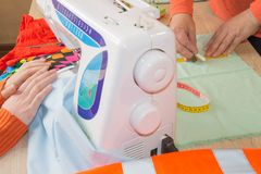 Mani della cucitrice sulla tavola di lavoro con nastro adesivo di misurazione Adatti le mani che funzionano con il panno del tess fotografia stock