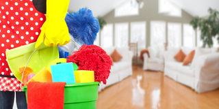 Mani della domestica con gli strumenti di pulizia