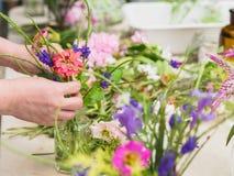 Mani della donna anziana che sistemano i fiori Fotografia Stock