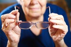 Mani della donna anziana con gli occhiali Immagini Stock