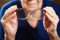 Mani della donna anziana con gli occhiali Fotografia Stock