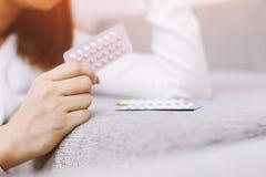 Mani della donna che aprono le pillole a disposizione Cibo della pillola anticoncezionale immagini stock