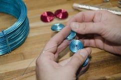 Mani della donna che creano un braccialetto Fotografia Stock