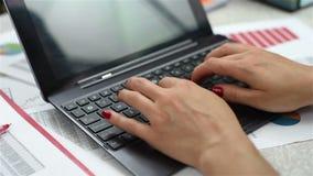 Mani della donna che digitano su un computer portatile video d archivio
