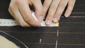 Mani della donna che fanno le marcature del gesso sul tessuto marrone del vestito archivi video