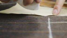 Mani della donna che fanno le marcature del gesso sul tessuto marrone del vestito stock footage
