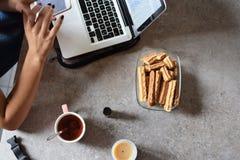 Mani della donna che funzionano con il computer portatile e lo smartphone immagini stock libere da diritti
