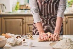 Mani della donna che impastano pasta sul tavolo da cucina Immagini Stock