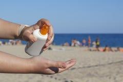 Mani della donna che mettono protezione solare nella spiaggia Fotografia Stock Libera da Diritti