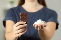 Mani della donna che mostrano zucchero e cioccolato immagine stock libera da diritti
