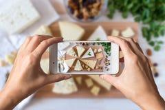 Mani della donna che prendono una foto dei generi differenti di formaggio delizioso fotografie stock libere da diritti