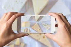 Mani della donna che prendono una foto dei generi differenti di formaggio delizioso immagini stock libere da diritti
