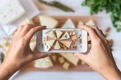 Mani della donna che prendono una foto dei generi differenti di formaggio delizioso con i dadi fotografie stock libere da diritti