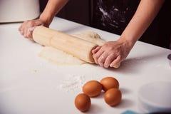 Mani della donna che producono pasta con il rotolamento di legno immagine stock