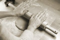 Mani della donna che rotolano pasta per i biscotti Fotografia Stock