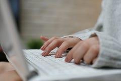 Mani della donna che scrivono sul computer portatile Fotografia Stock