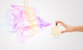 Mani della donna che spruzzano profumo Immagini Stock