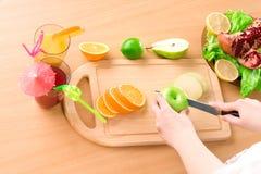 Mani della donna che tagliano mela Fotografia Stock Libera da Diritti