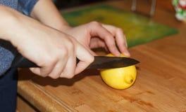 Mani della donna che tagliano un grande limone giallo un coltello da cucina fotografia stock libera da diritti