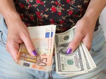 Mani della donna che tengono i dollari e gli euro Fotografie Stock