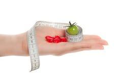 Mani della donna che tengono pomodoro verde, pillole Fotografie Stock
