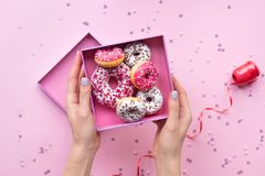 Mani della donna che tengono scatola aperta con le guarnizioni di gomma piuma variopinte su fondo rosa fotografie stock