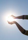Mani della donna che tengono sole Immagine Stock