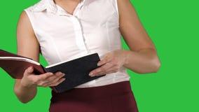 Mani della donna che tengono taccuino e che girano le pagine che lo esaminano su uno schermo verde, chiave di intensità video d archivio
