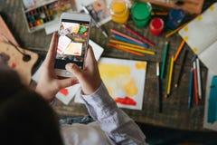 Mani della donna che tengono telefono cellulare che prende le foto del lavoro dell'acquerello Processo creativo dell'artista di l immagini stock libere da diritti
