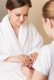 Mani della donna in ciotola di vetro con acqua sull'asciugamano bianco Fotografia Stock