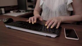 Mani della donna con i chiodi gialli che scrivono sulla tastiera Il telefono cellulare è sulla tavola di legno archivi video