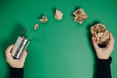 Mani della donna con il barattolo di alluminio e la carta sgualcita su una parte posteriore di verde Immagini Stock