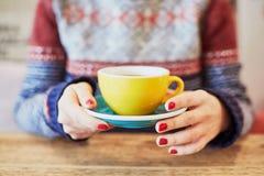 Mani della donna con il manicure e la tazza di caffè rossi Fotografie Stock