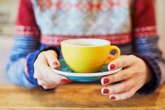 Mani della donna con il manicure e la tazza rossi di caffè caldo fresco sulla tavola di legno Fotografie Stock