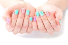 Mani della donna con il manicure luminoso Immagini Stock