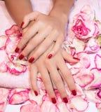 Mani della donna con il manicure rosso Immagini Stock