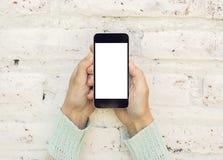 Mani della donna con il telefono cellulare in bianco fotografia stock libera da diritti
