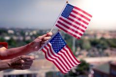 Mani della donna con la bandiera nazionale di U.S.A. Fotografie Stock