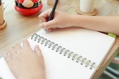 Mani della donna con scrittura della penna sul taccuino Fotografie Stock Libere da Diritti