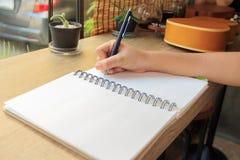 Mani della donna con scrittura della penna sul taccuino Immagine Stock
