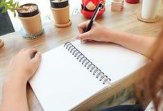 Mani della donna con scrittura della penna sul taccuino Immagini Stock