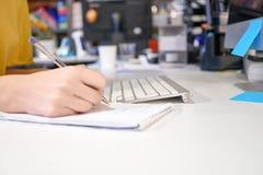 Mani della donna con scrittura della penna sul taccuino all'ufficio fotografia stock