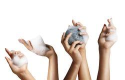 Mani della donna con una schiuma del sapone Immagine Stock