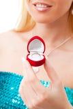 Mani della donna del biglietto di S. Valentino con l'anello in casella rossa immagine stock libera da diritti