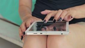 Mani della donna del primo piano facendo uso del computer digitale della compressa Colpo del carrello video d archivio