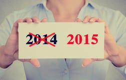 Mani della donna di affari che tengono segno con gli anni 2014 attraversati e 2015 segnati Fotografie Stock Libere da Diritti