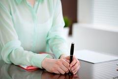 Mani della donna di affari in una blusa verde che si siede allo scrittorio nell'ufficio e che tiene penna scura, la finestra gius Fotografie Stock Libere da Diritti