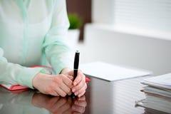Mani della donna di affari in una blusa verde che si siede allo scrittorio nell'ufficio e che tiene penna scura, la finestra gius Fotografia Stock Libera da Diritti