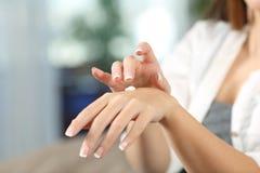 Mani della donna di bellezza che si idratano con la crema dell'idratante Immagine Stock Libera da Diritti