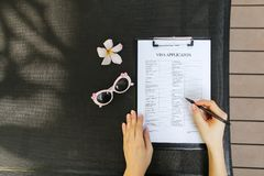 Mani della donna di disposizione, penna e domanda di visto piane di viaggio, sunli Fotografia Stock